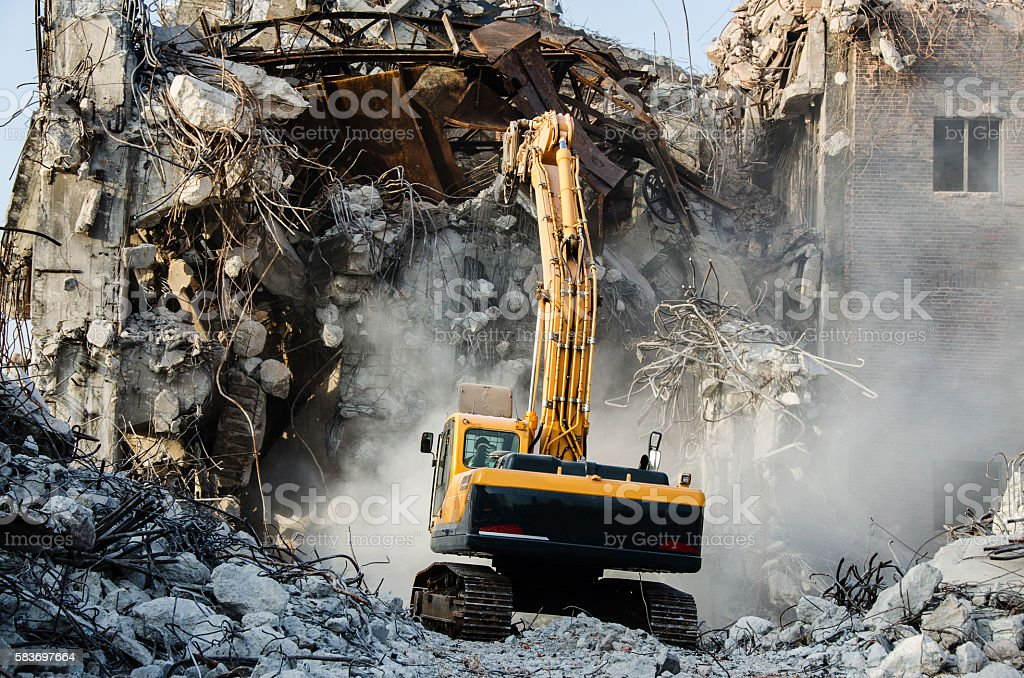 Excavator working at the demolition of an old industrial buildin stock photo