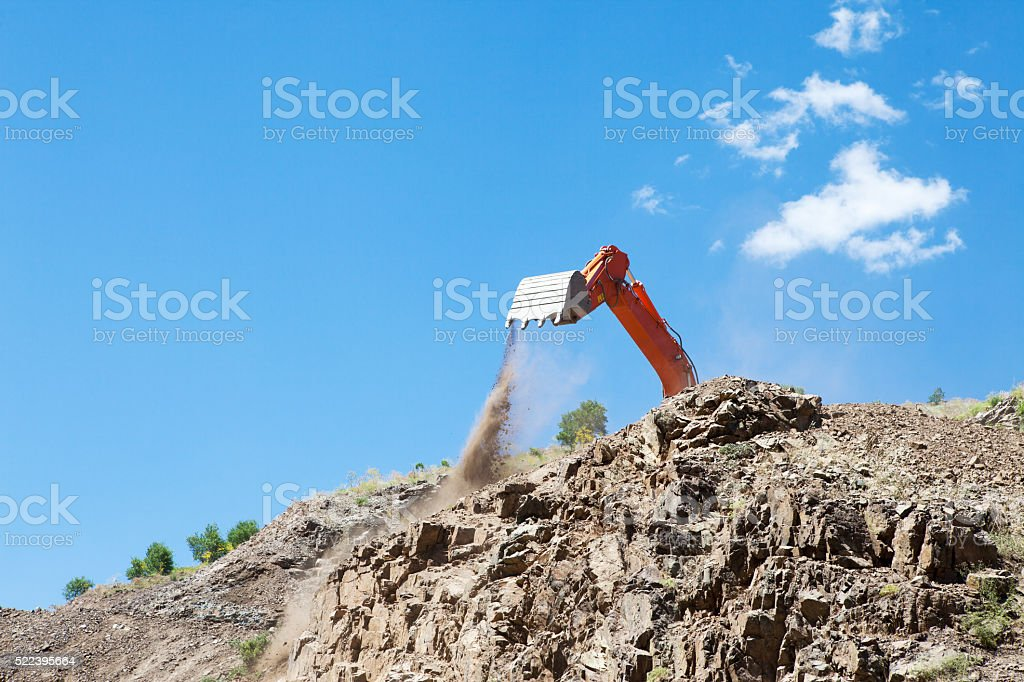 Excavator working in the mountains. stock photo