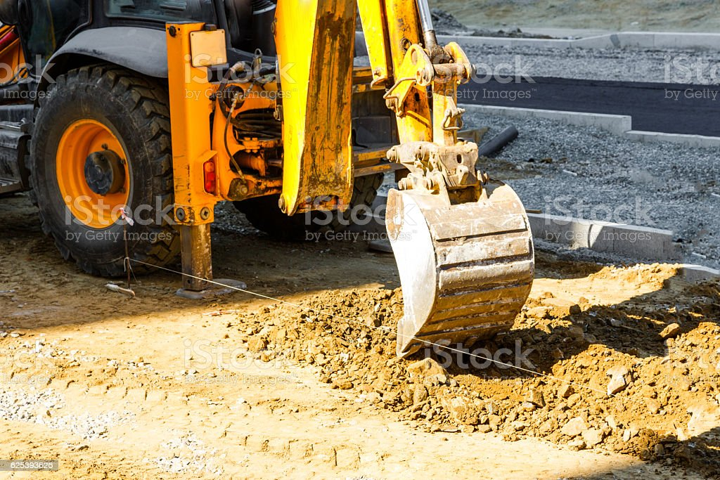 Excavator working outside on road construction stock photo