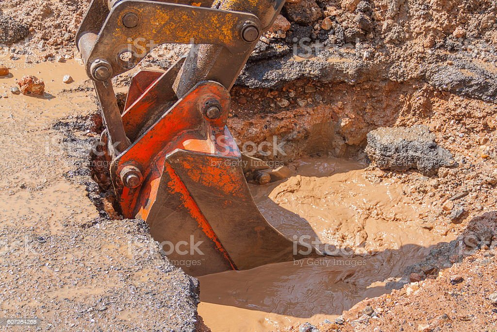 Excavator working the Repair of  pipe on  road stock photo