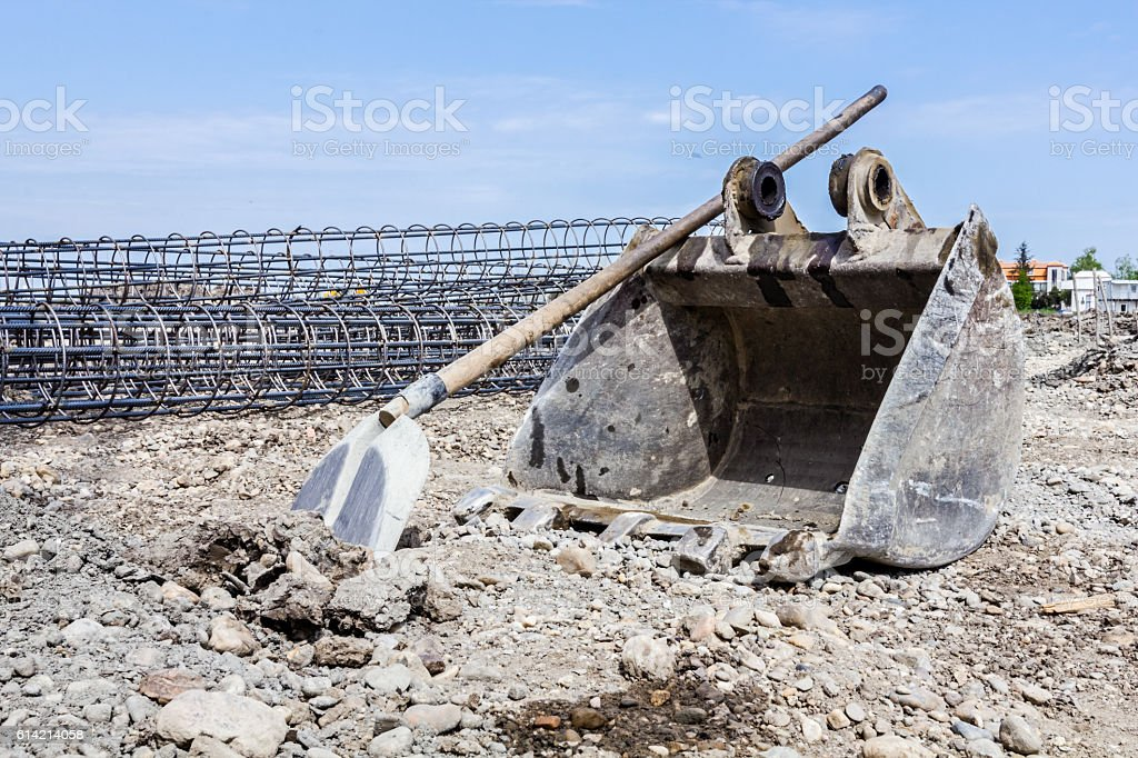 Excavator's bucket and shovel in front of skeleton reinforcing s stock photo