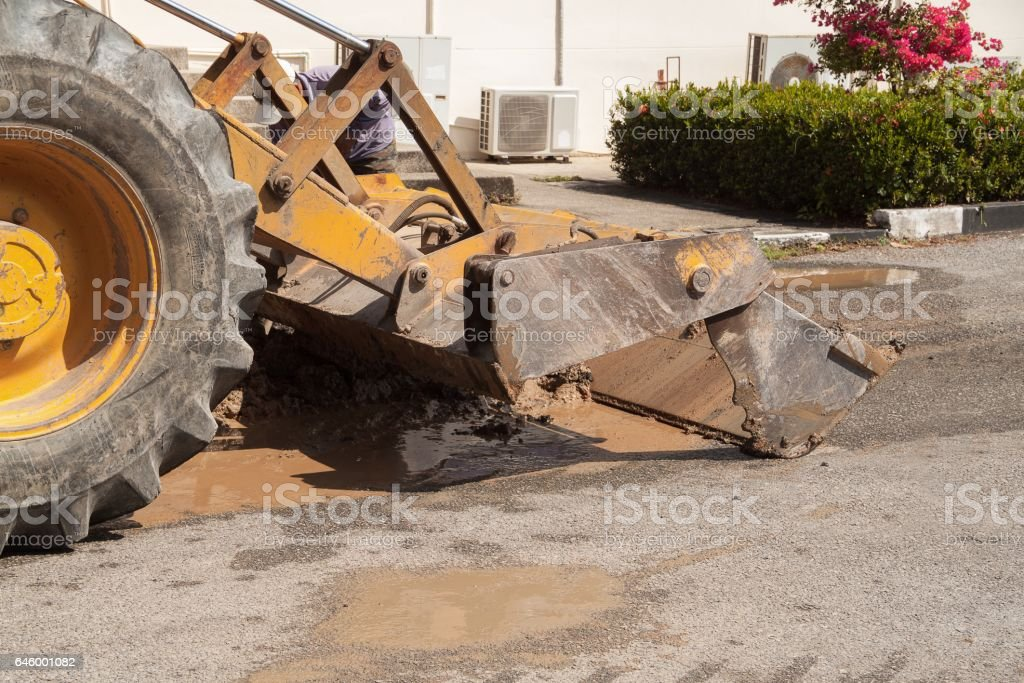 Excavators, bulldozer work a hole the repair of pipe water and sewerage on road stock photo