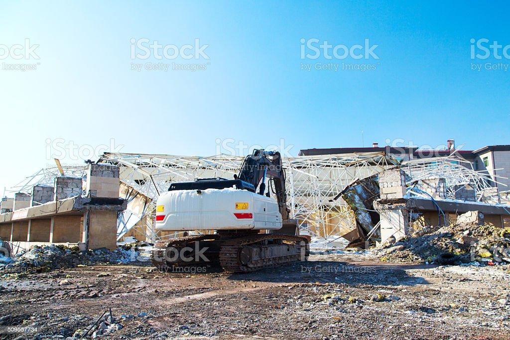 Excavators destroy the old building demolition stock photo