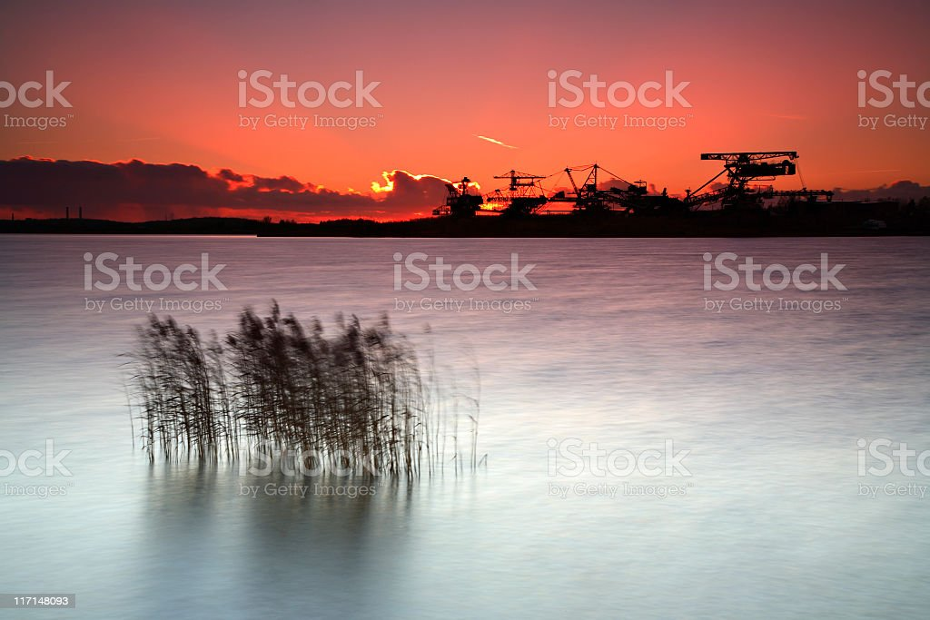 Excavators on abandoned Open Pit Mine by Lake at Sunset royalty-free stock photo