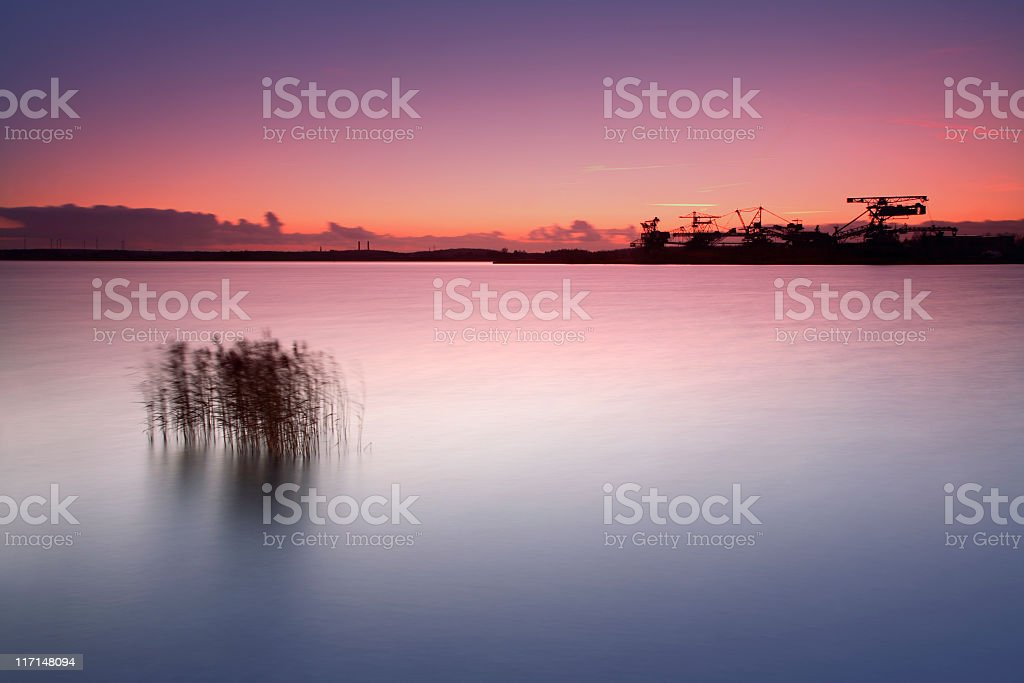 Excavators on abandoned Open Pit Mine by Lake at Sunset stock photo