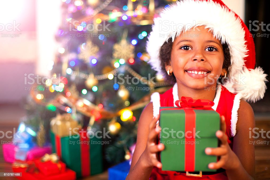 Excited African American child holding wrapped Christmas present stock photo