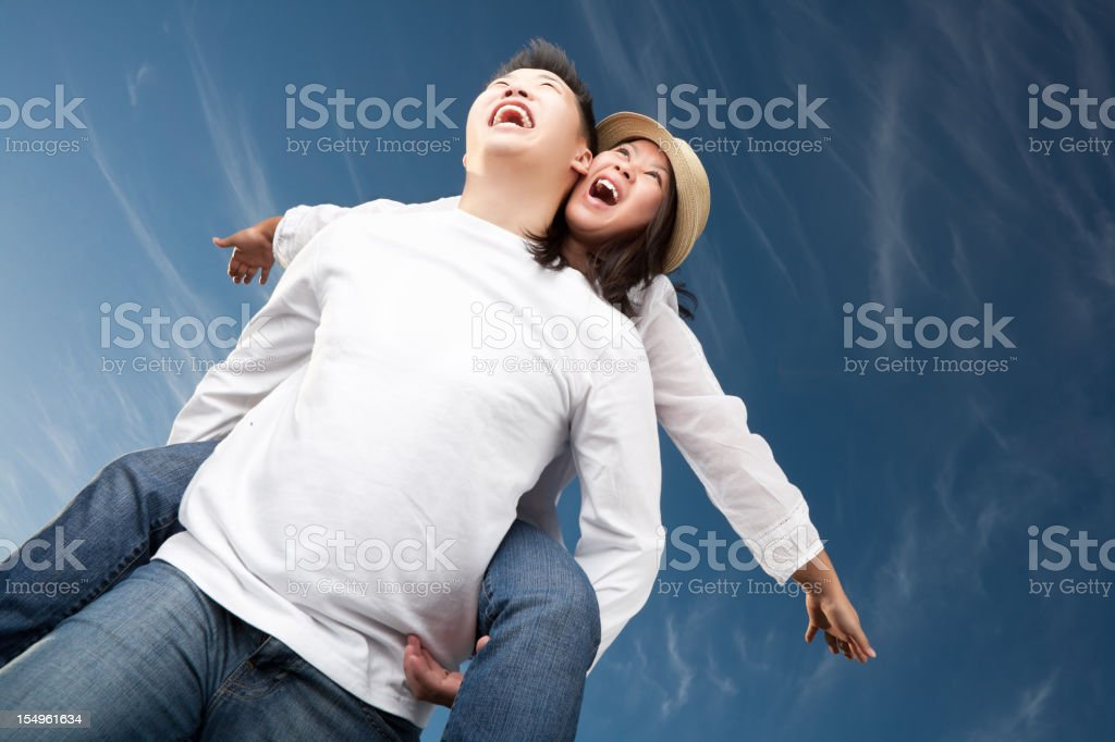 Excited asian couple against blue sky royalty-free stock photo