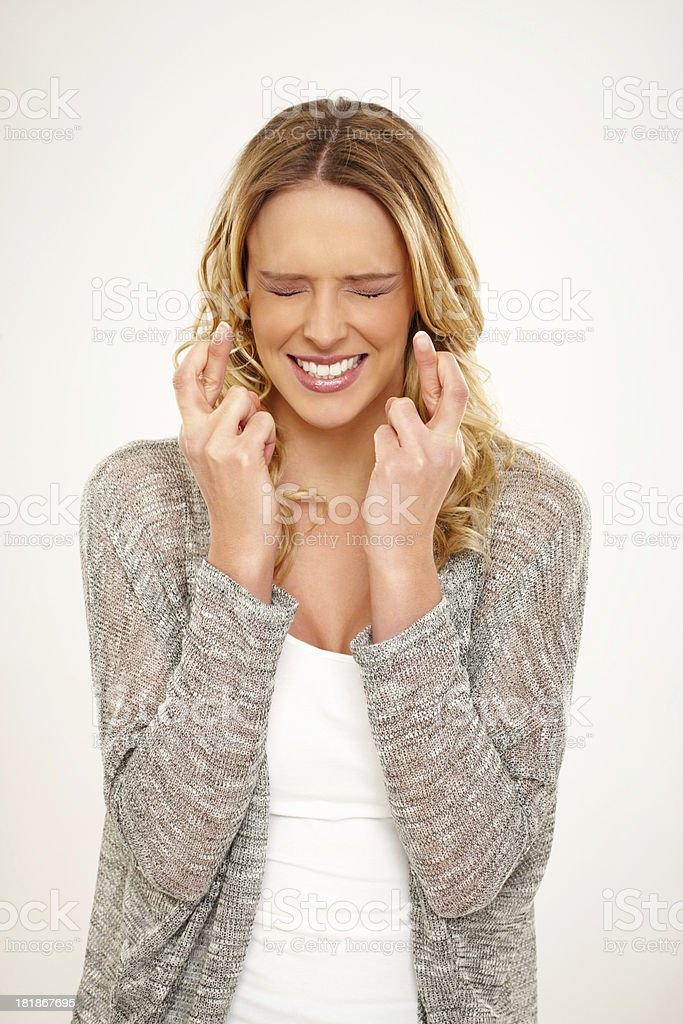 Excited beautiful young woman with fingers crossed stock photo