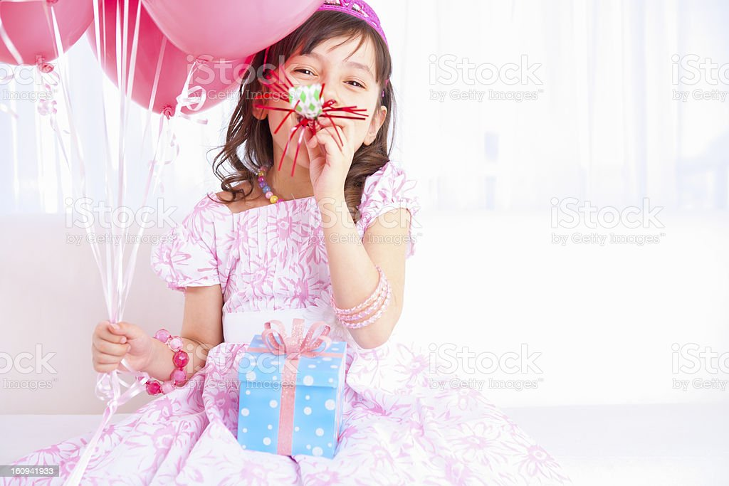 Excited birthday girl playing with a party horn blower stock photo
