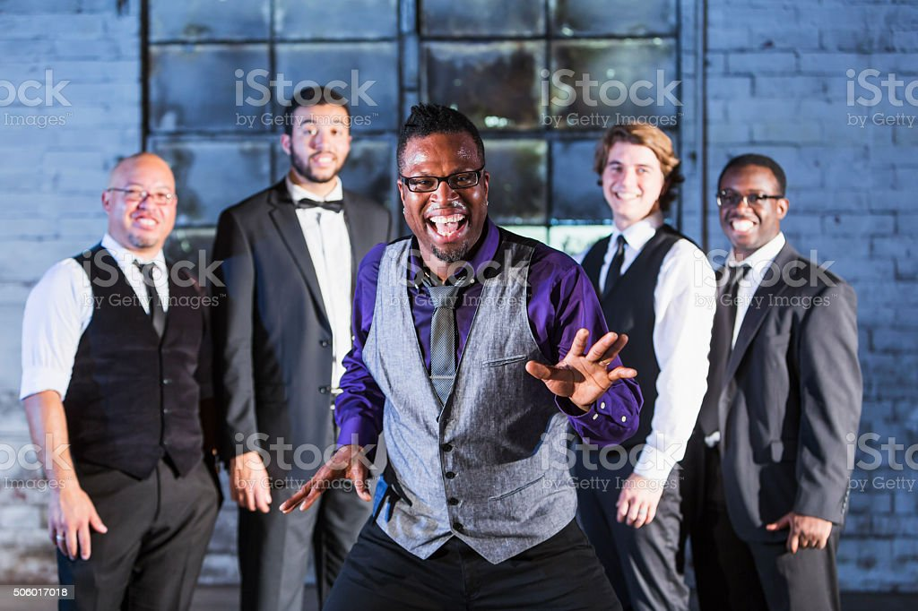 Excited black man laughing, standing in front of group stock photo