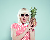 Excited blonde young woman holding pineapple