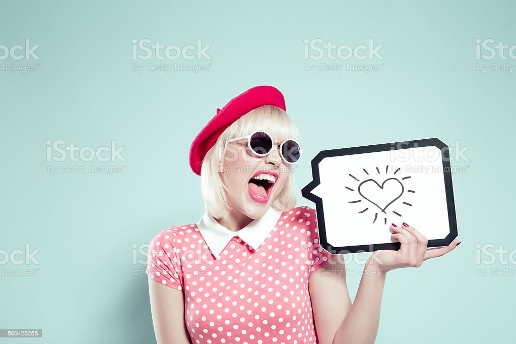 Excited blonde young woman holding speech bubble with drawn heart stock photo