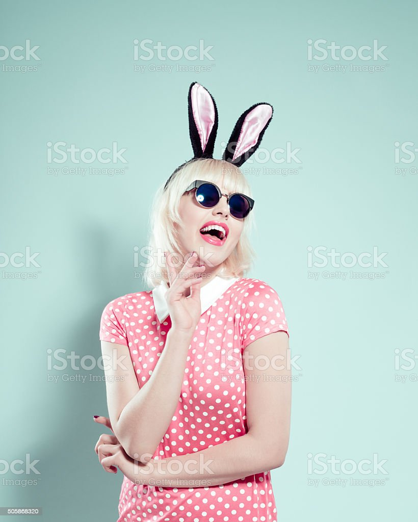 Excited blonde young woman wearing rabbit ears headband and sunglasses stock photo