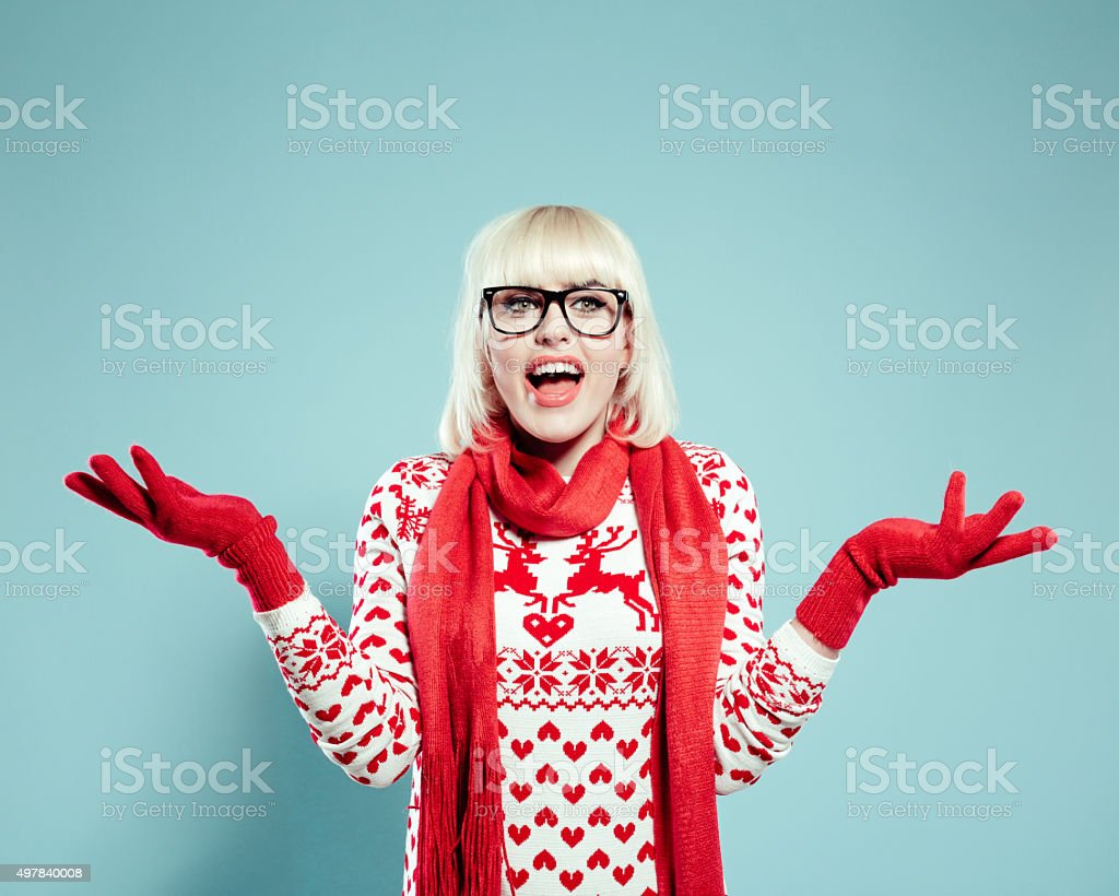 Excited blonde young woman wearing xmas sweater, scarf and gloves stock photo