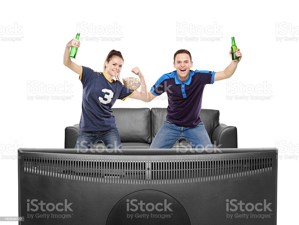 Excited boy and girl watching sport on a TV royalty-free stock photo