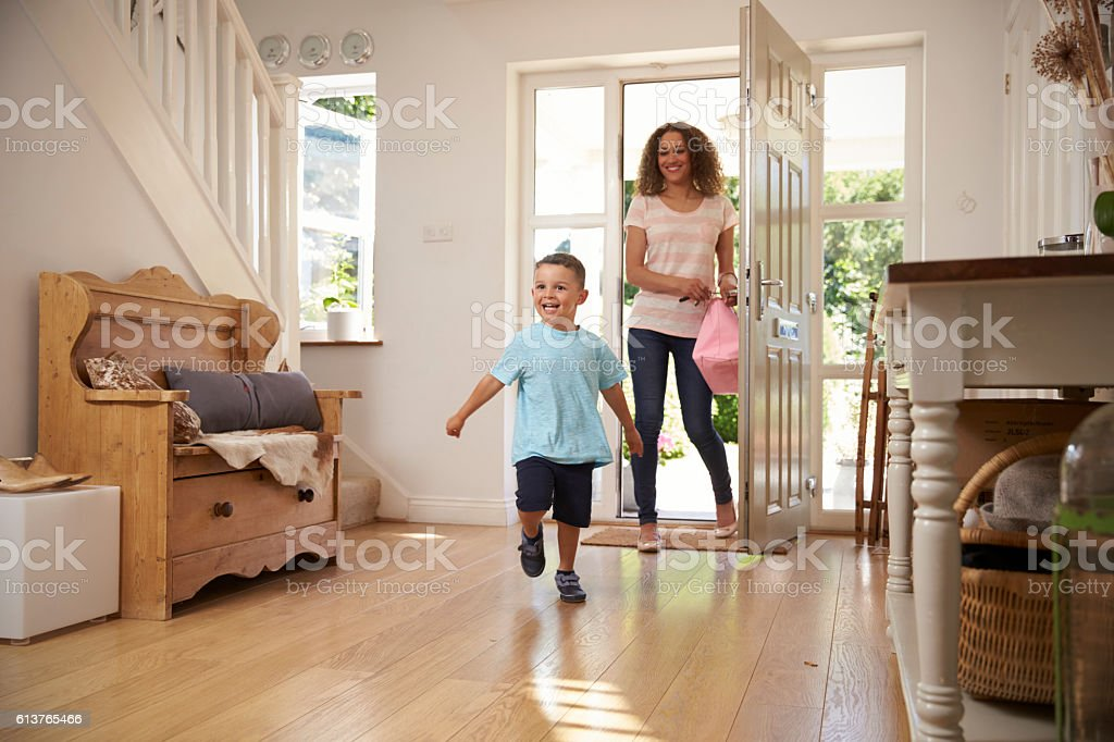 Excited Boy Returning Home From School With Mother stock photo