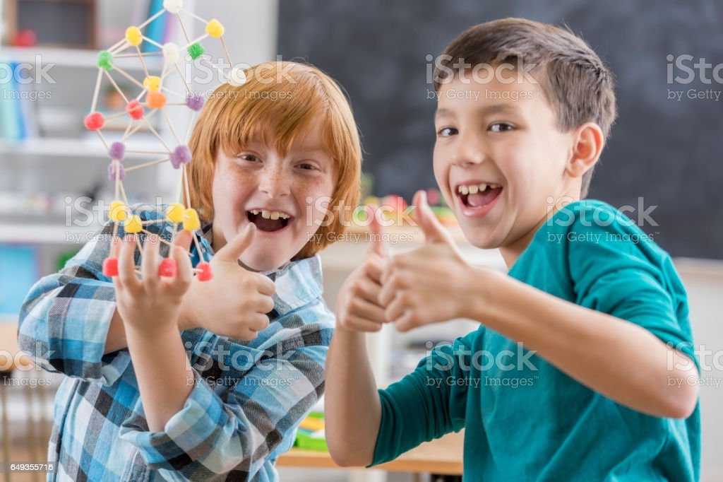 Excited boys complete fun engineering project at school stock photo