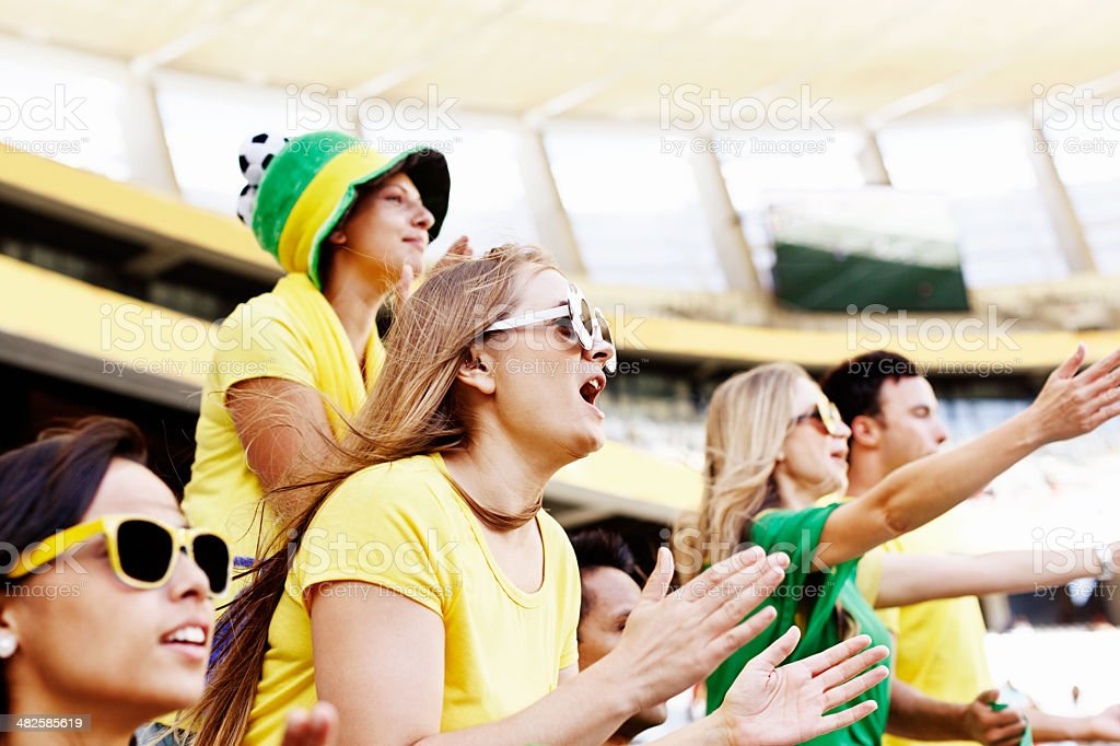 Excited Brazilian soccer fans wave and cheer at match stock photo