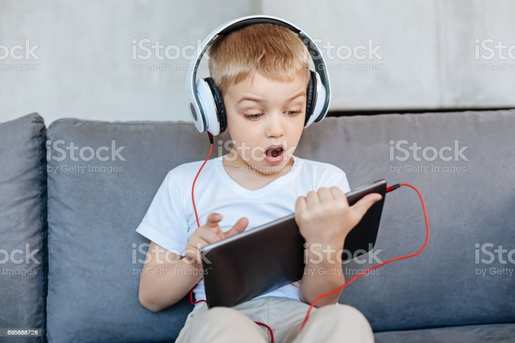 Excited bright boy finding something interesting in the internet stock photo