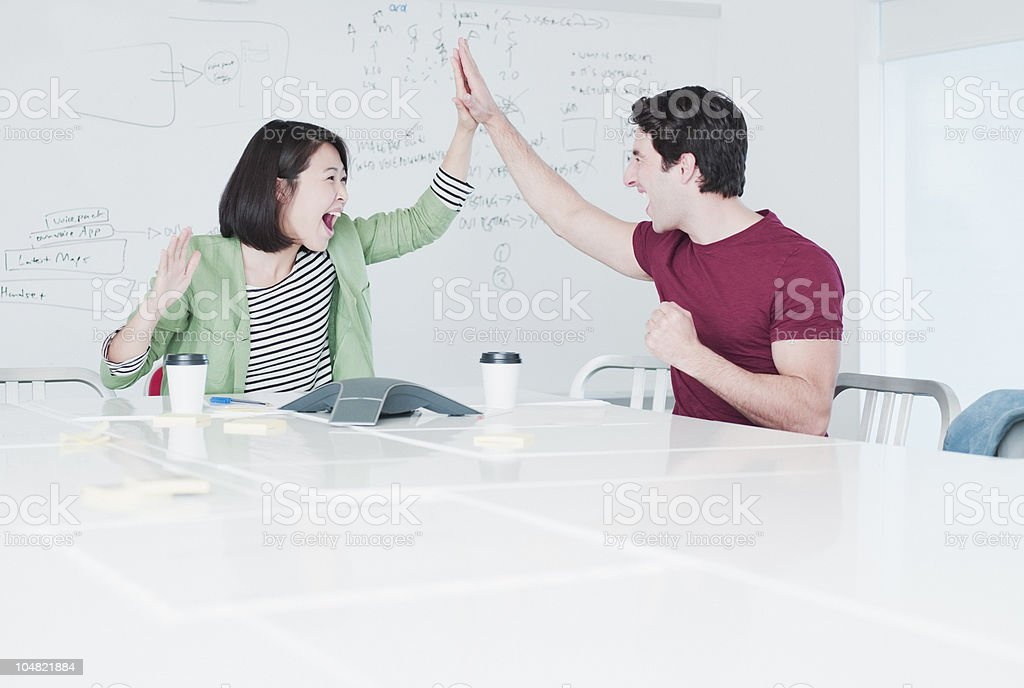 Excited business people giving high five in conference room royalty-free stock photo
