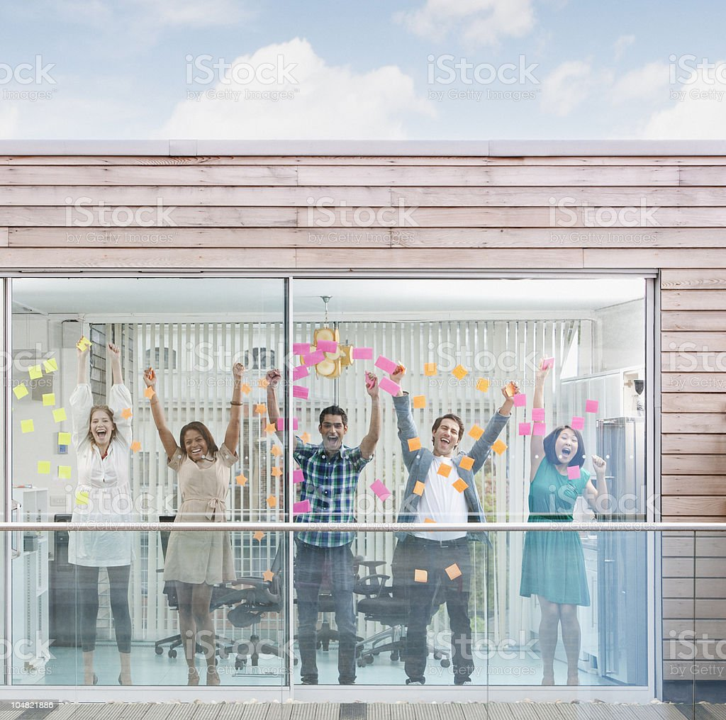 Excited business people with arms raised at window covered in adhesive notes royalty-free stock photo