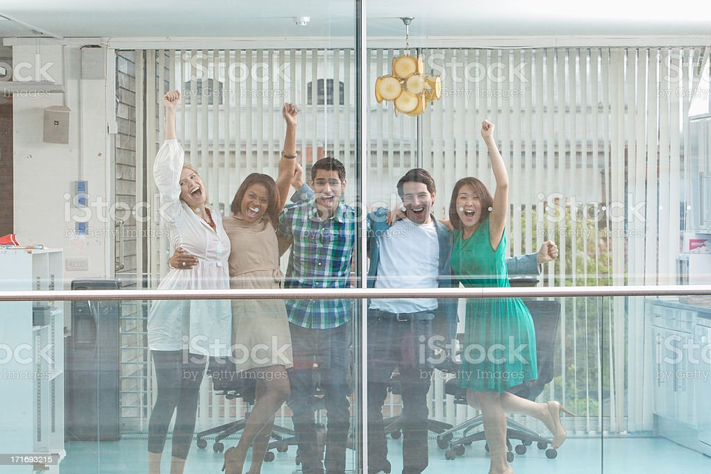 Excited business people with arms raised at window