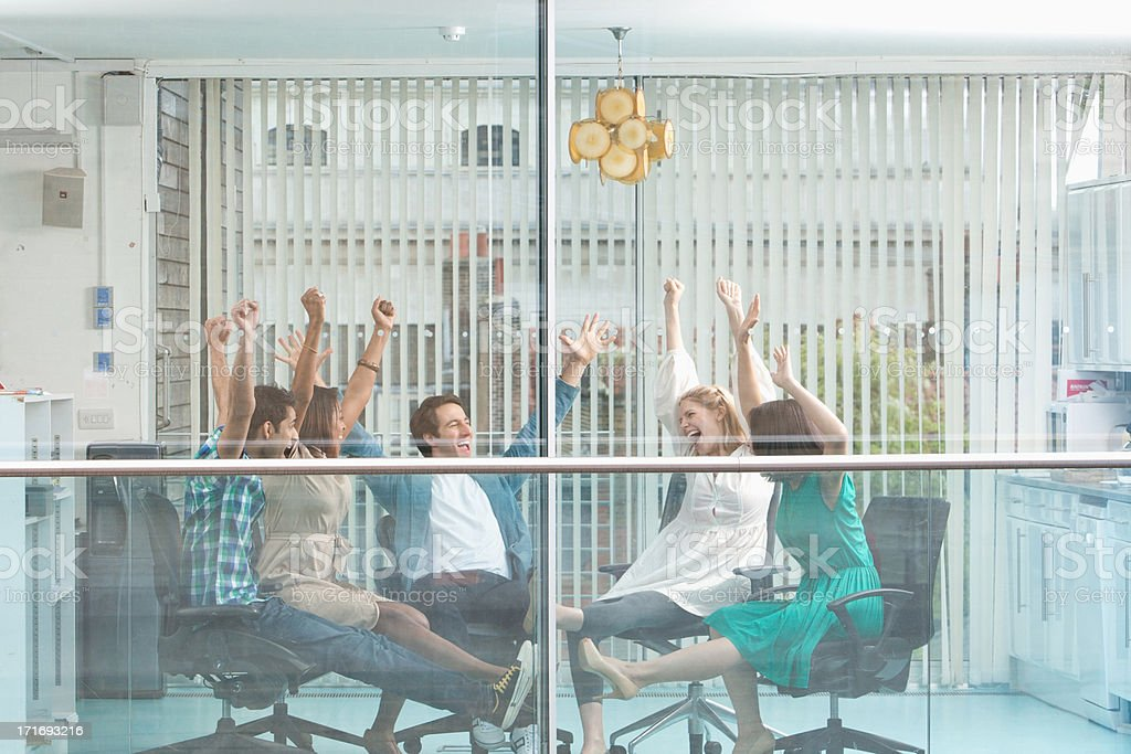 Excited business people with arms raised at window  stock photo