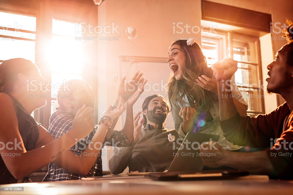 Excited business team celebrating their success at office. stock photo