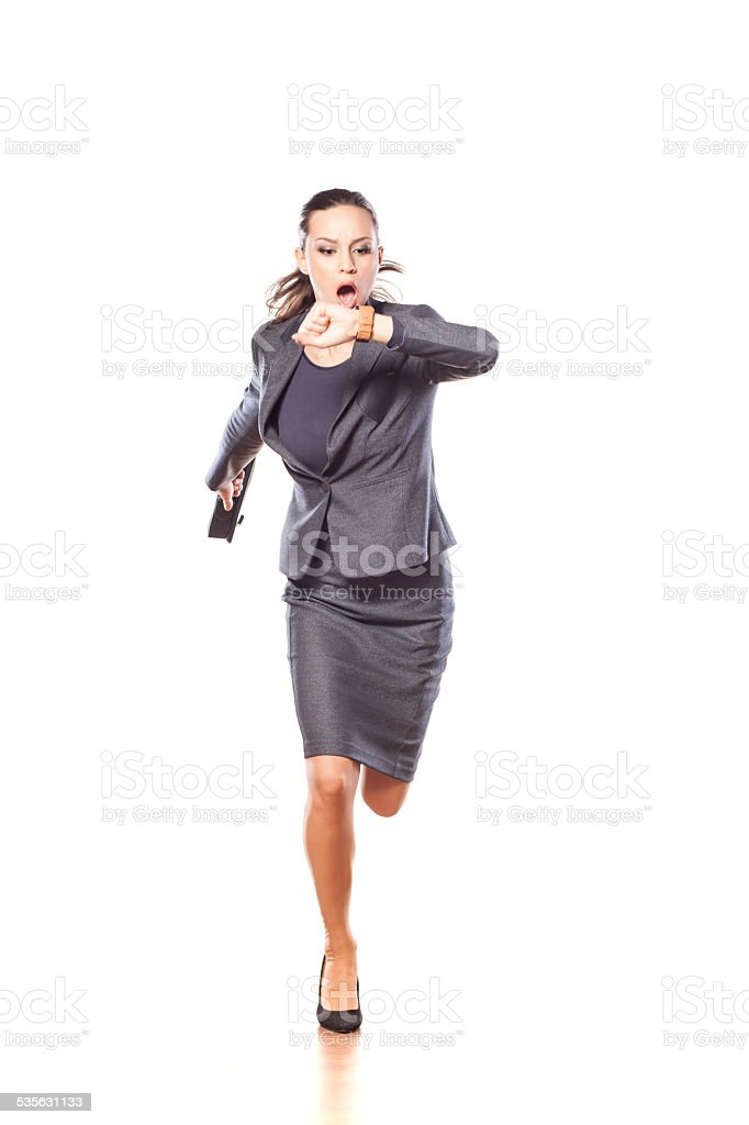 Excited business woman running and looking at her watch stock photo