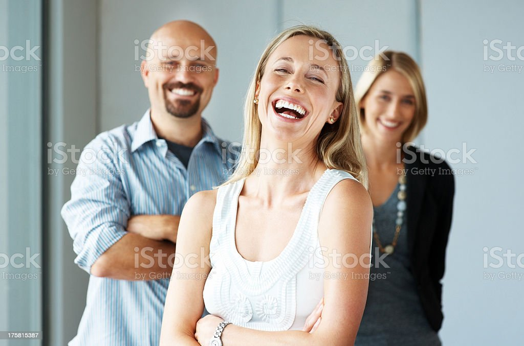 Excited business woman with colleagues at the back stock photo