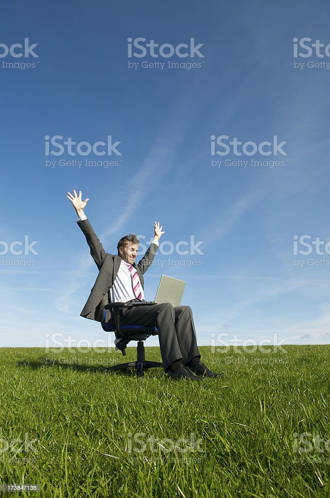 Excited Businessman Celebrating with Laptop Sitting in Meadow royalty-free stock photo