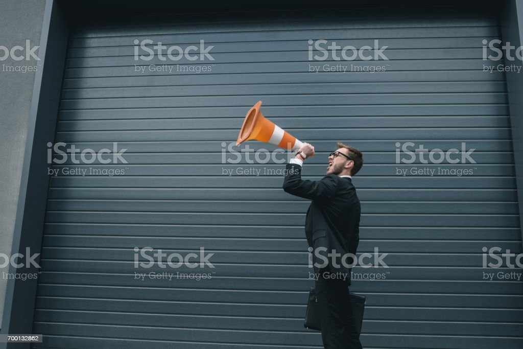 Excited businessman in eyeglasses holding briefcase and shouting in traffic cone stock photo