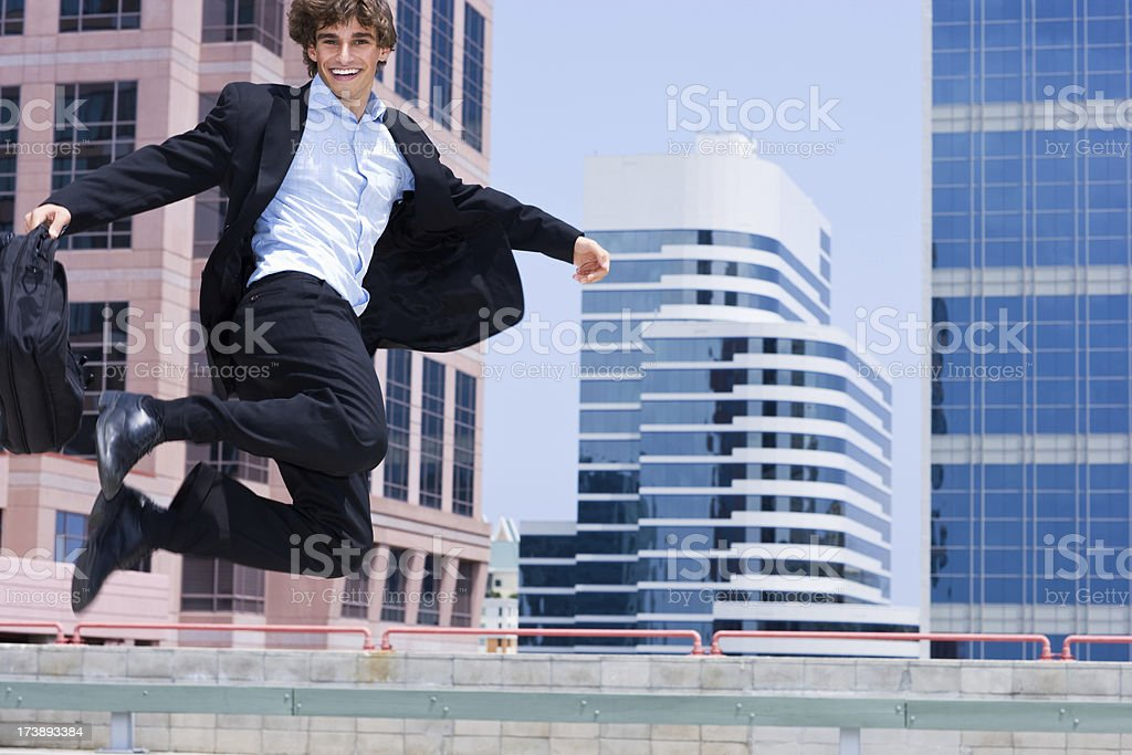 Excited businessman jumping in the air surrounded by buildings royalty-free stock photo