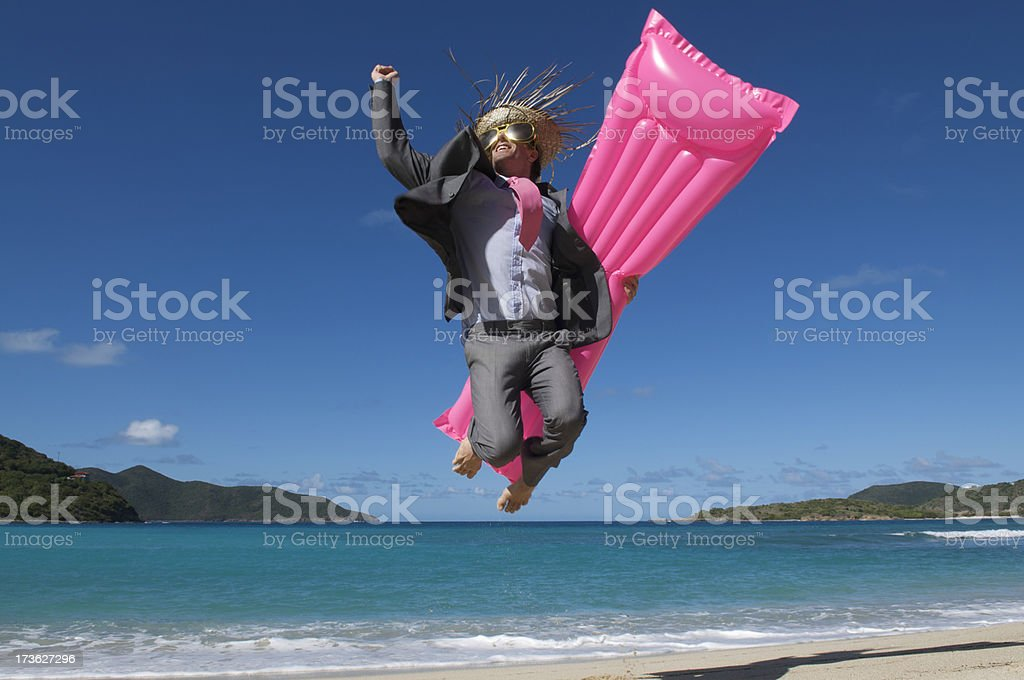 Excited Businessman Jumping on Tropical Beach with Pink Air Mattress royalty-free stock photo