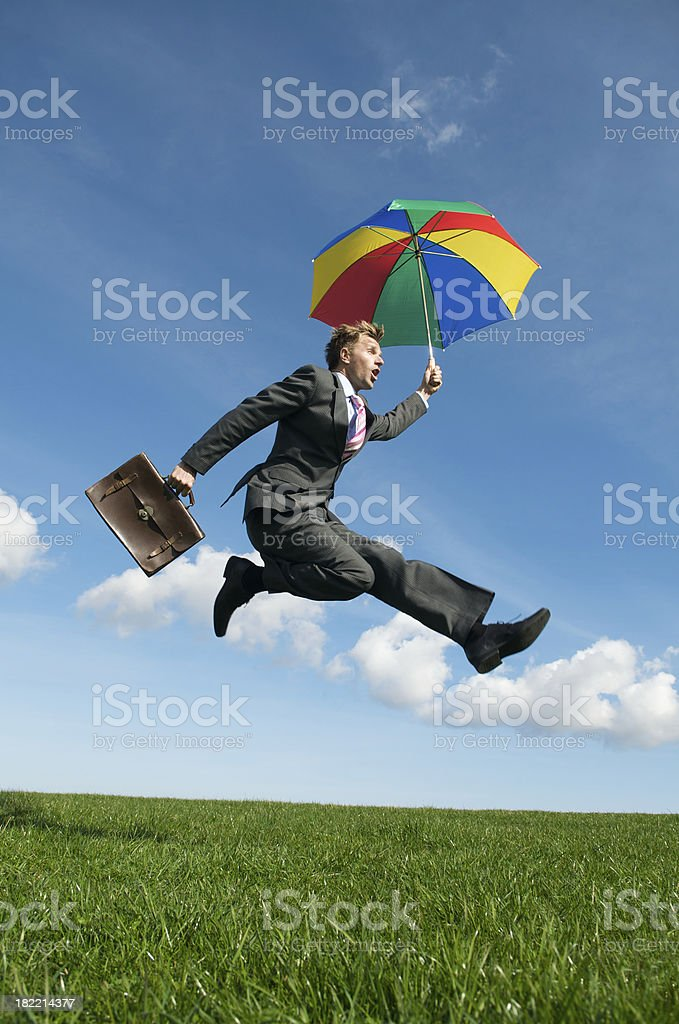 Excited Businessman Jumping with Umbrella in Green Meadow royalty-free stock photo