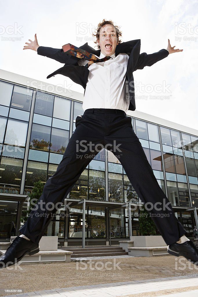 Excited businessman jumps for joy outside modern office stock photo