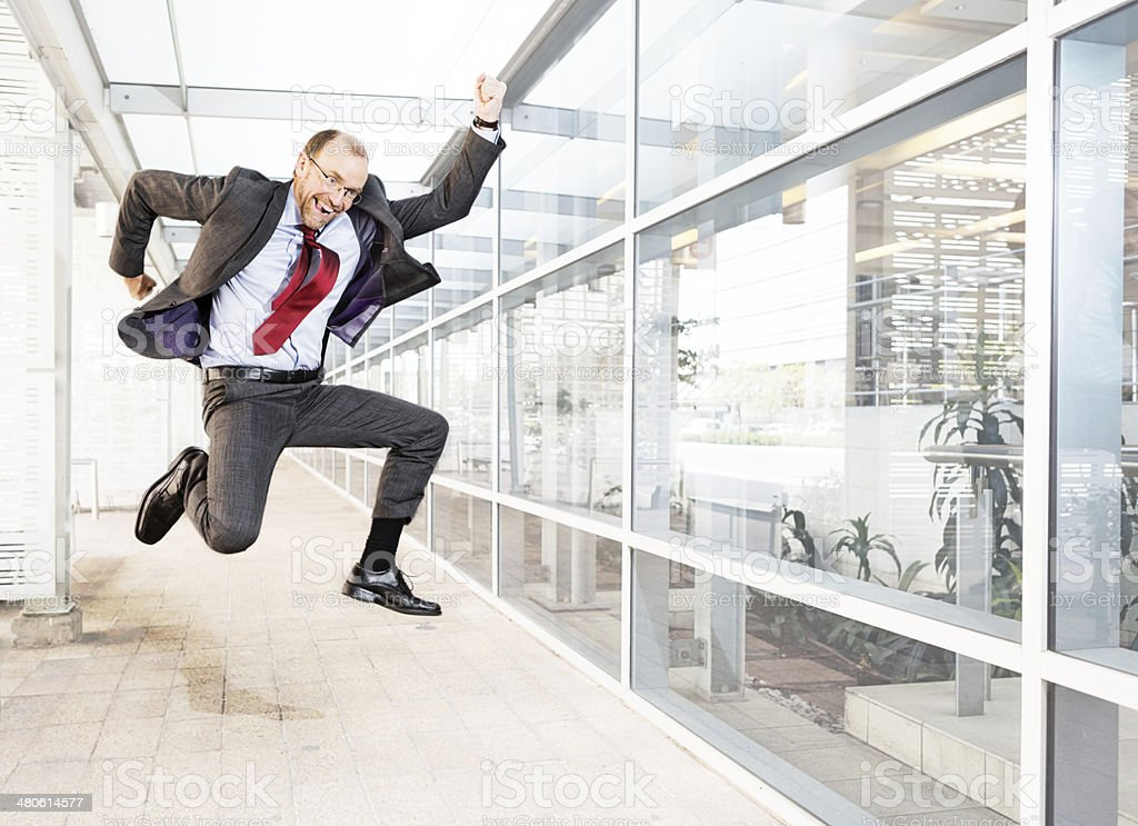Excited businessman leaps happily into the air outside office building stock photo