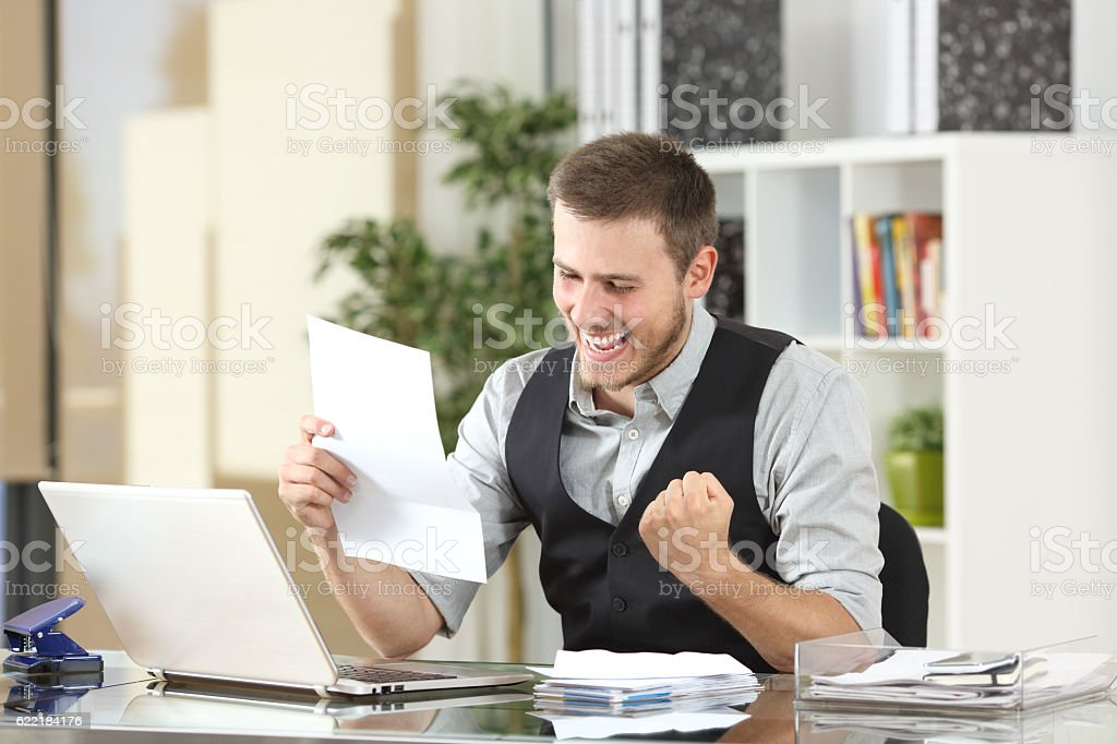 Excited businessman reading a letter at office stock photo
