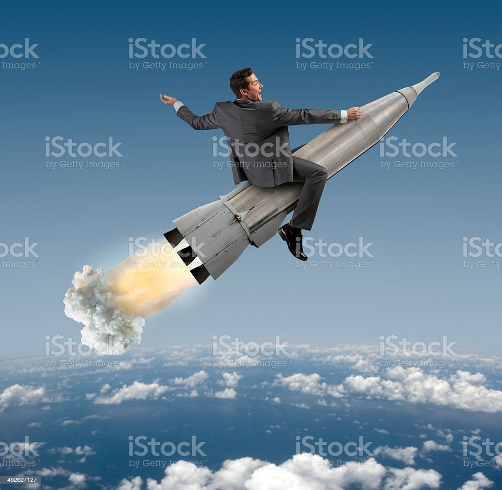 Excited Businessman Riding On A Rocket stock photo