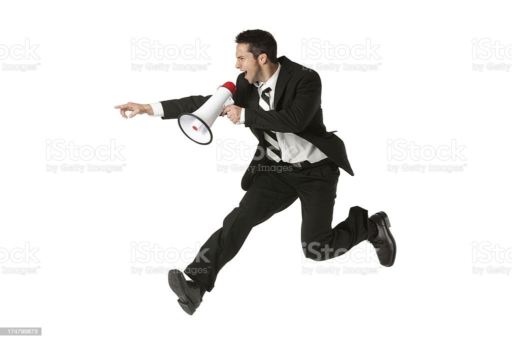 Excited businessman shouting into a bullhorn royalty-free stock photo
