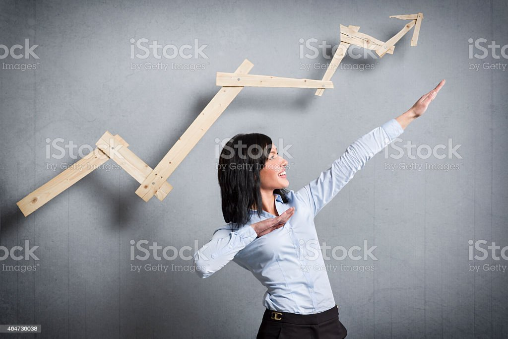 Excited businesswoman in front of pointing up business chart. stock photo