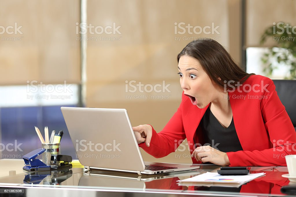 Excited businesswoman watching amazing news stock photo