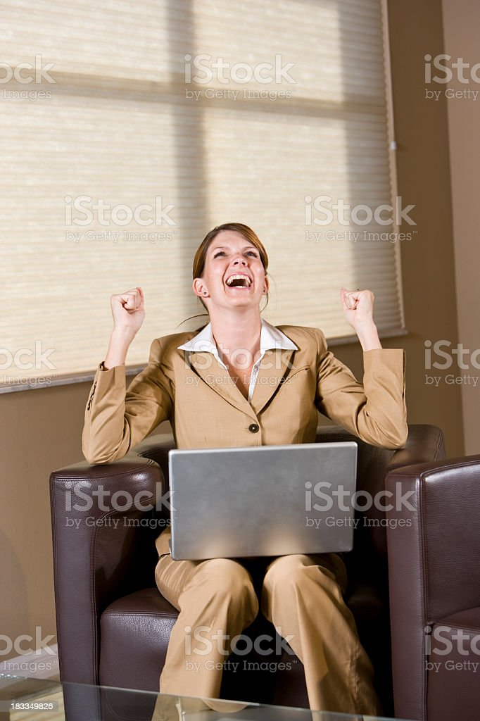 Excited businesswoman with raised fists, laptop on lap stock photo
