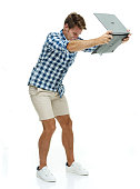 Excited casual man throwing laptop