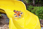 excited children in water park riding on slide with float