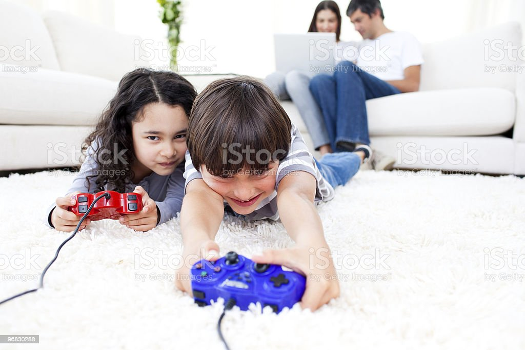 Excited children playing video games lying on the floor royalty-free stock photo