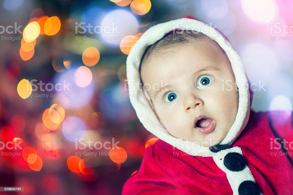 Excited Christmas Helper Baby in Santa Clothes stock photo