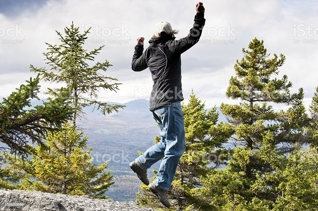 Excited climber jumping at the top of a mountain stock photo