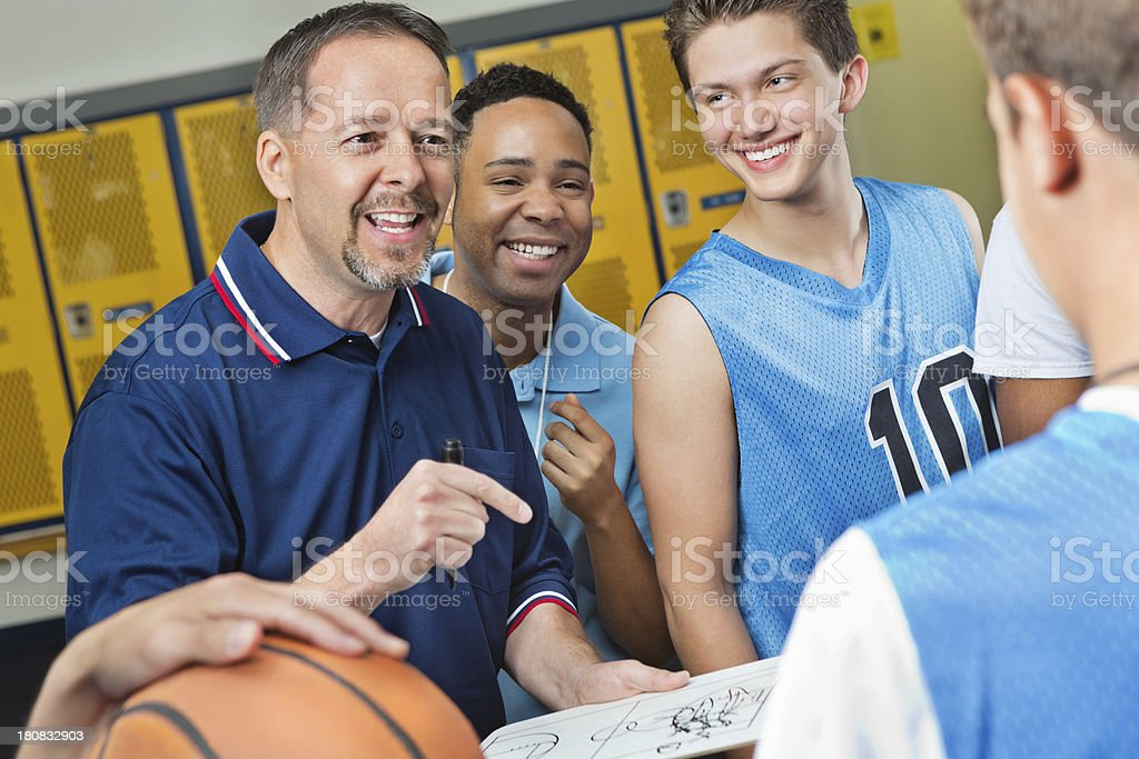Excited coach and assistant explaining play to basketball player stock photo