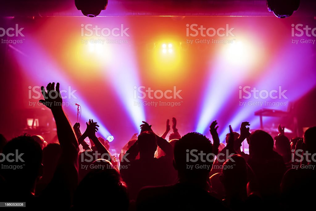 Excited concert crowd and colorful light show at scenario stock photo